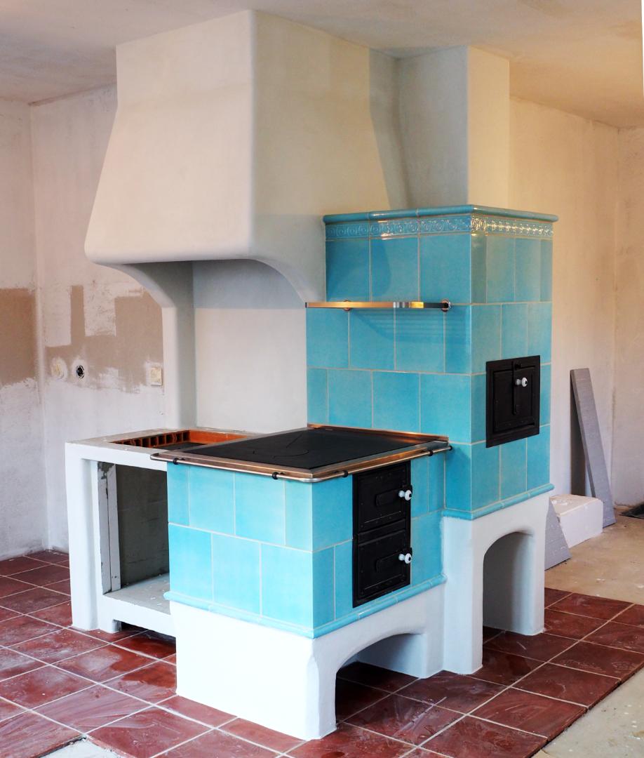 Modry kachlovy sporak s murovanym digestorom a pripravou na sklokeramicku platnu.